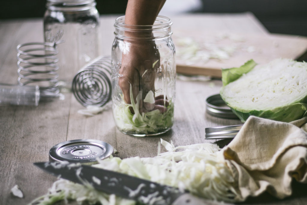 a hand punching down cabbage into sauerkraut