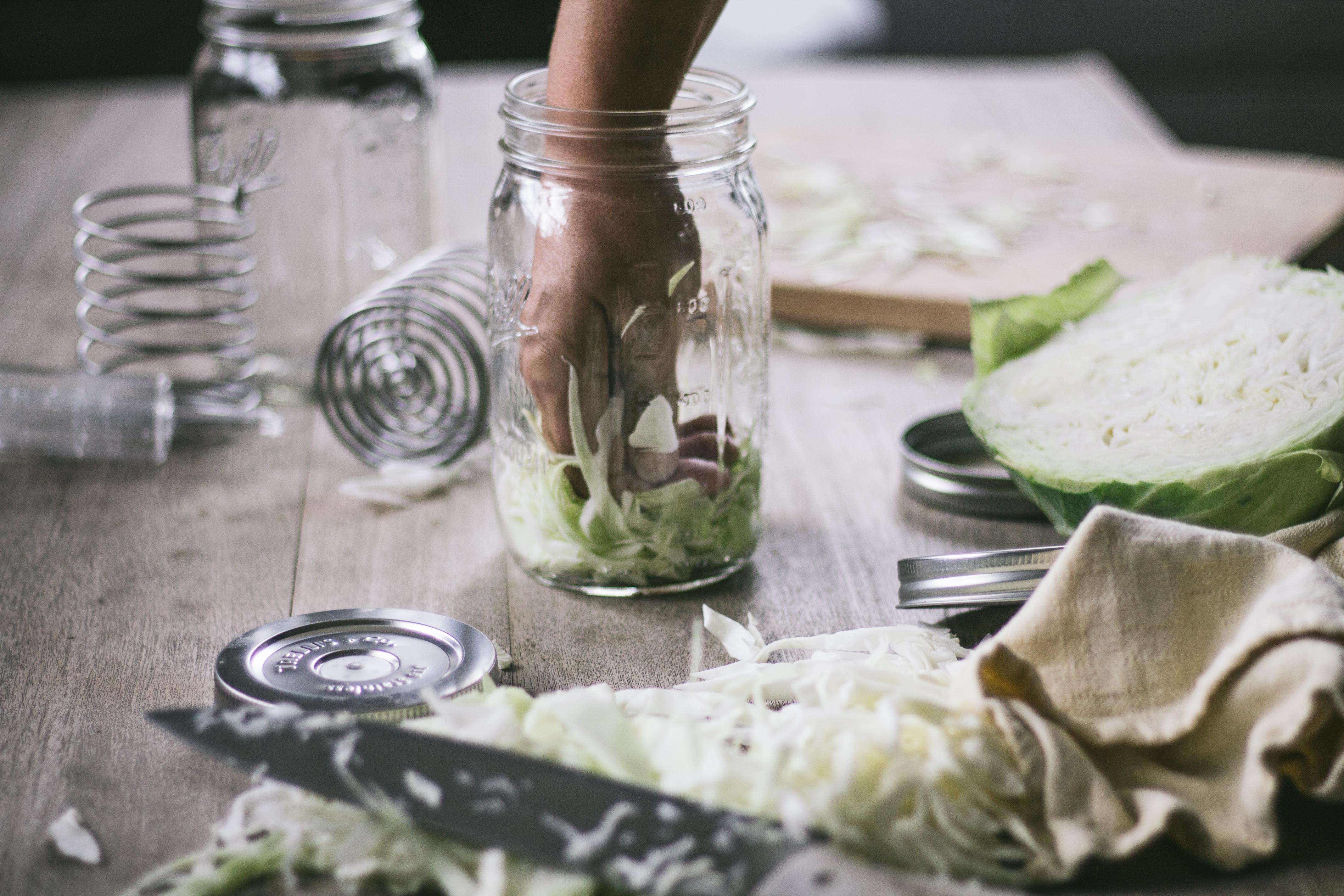 a hand making sauerkraut in a mason jar