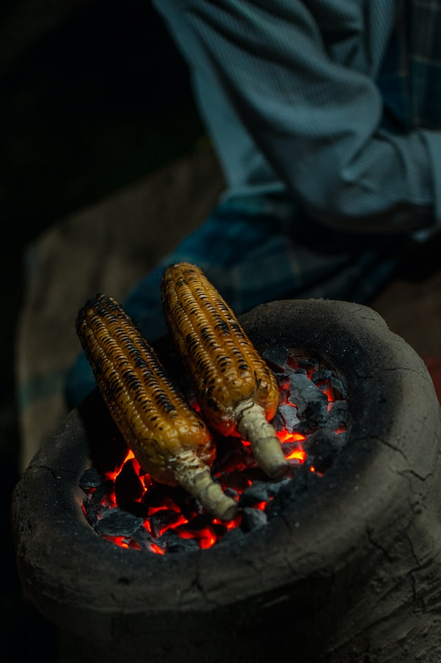 corn on the cob being cooked directly on fire coals
