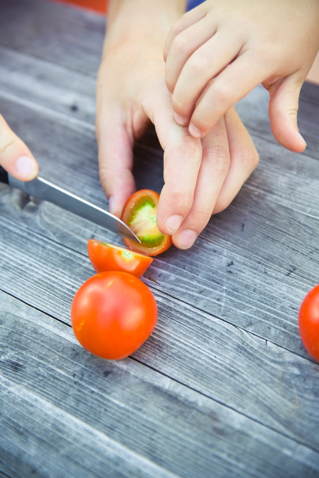 two hands cutting a tomato