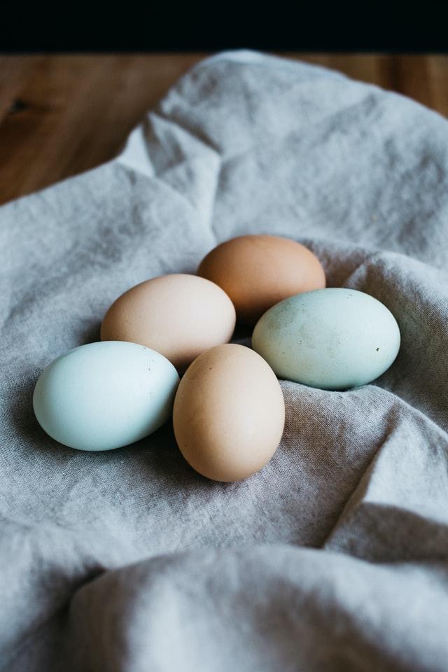 several multi-colored eggs on a linen cloth