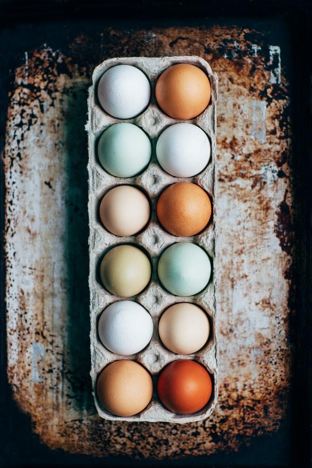 multi-colored eggs in a cardboard carton