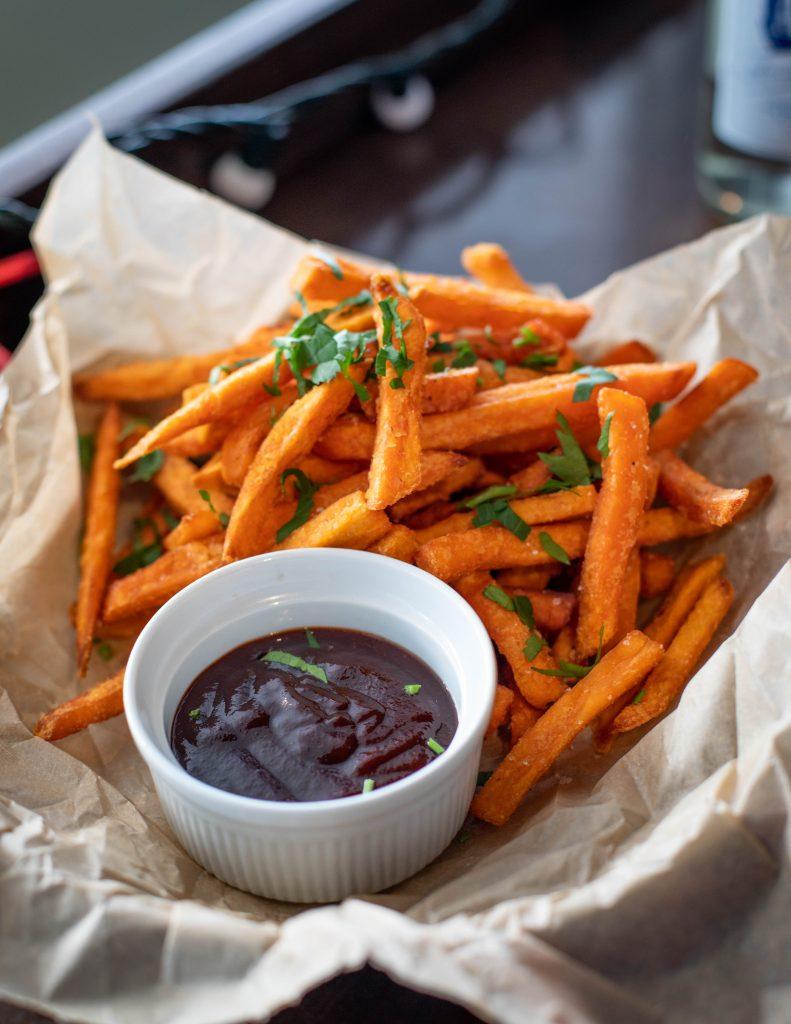 homemade bbq sauce next to sweet potato fries