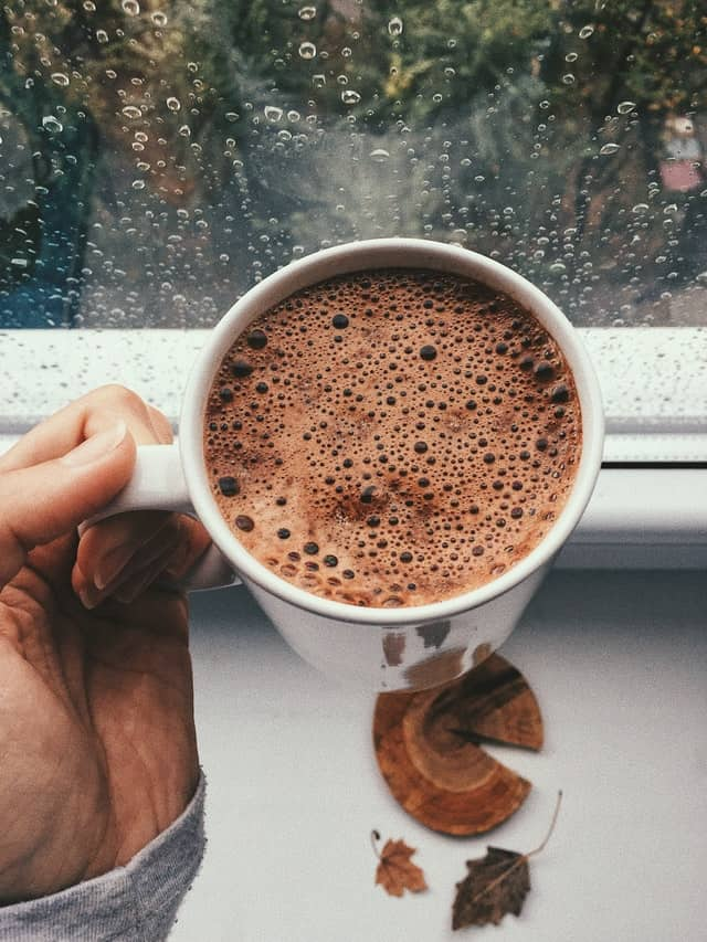 a hand holding a mug of instant hot chocolate