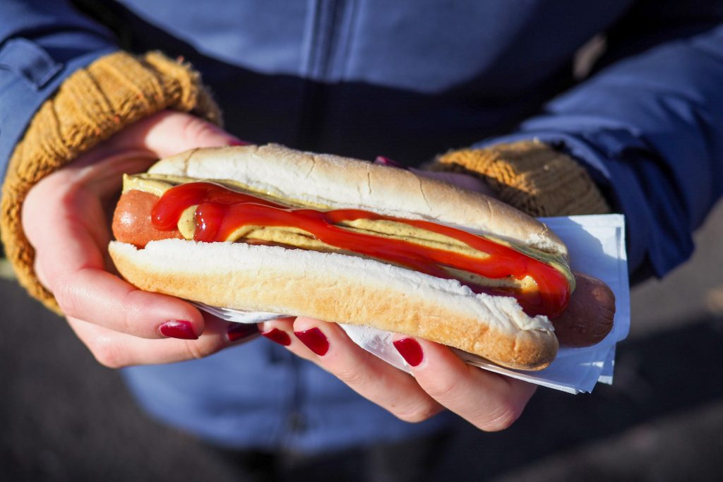woman holding a hot dog with homemade ketchup made from fresh tomatoes
