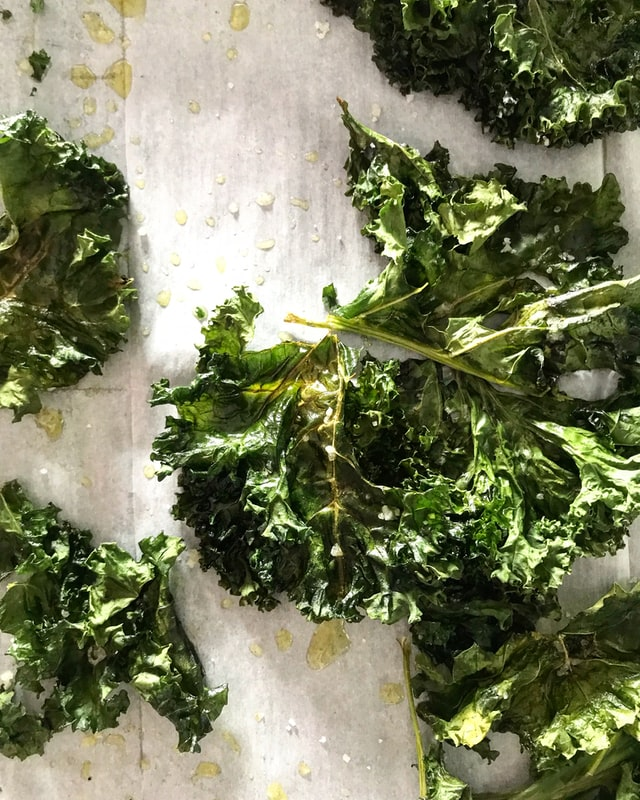 kale leaves drenched in olive oil and sea salt on a cookie sheet
