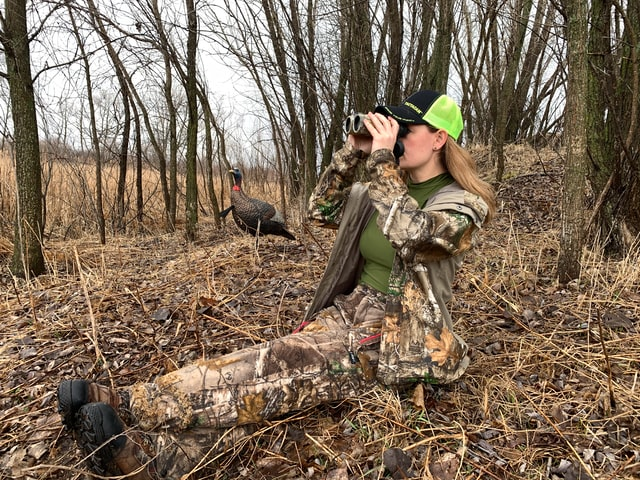 woman in camo using a pair of binoculars while hunting