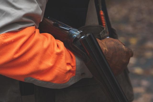 blaze orange hunting gear and shotgun