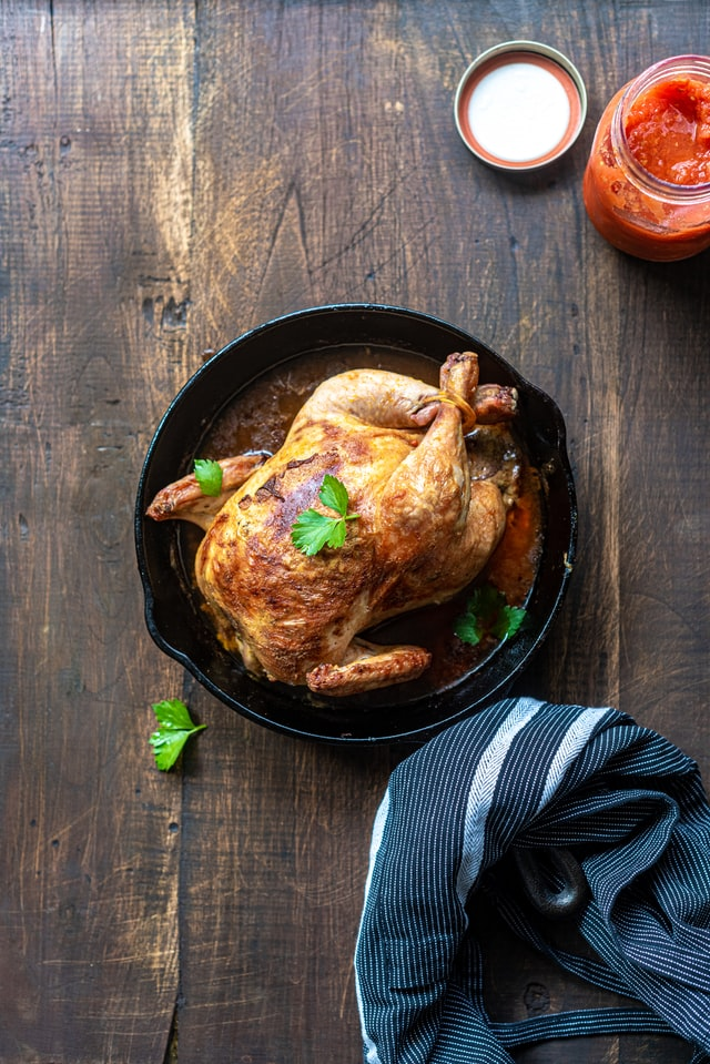 a whole chicken roasted in a cast iron pan