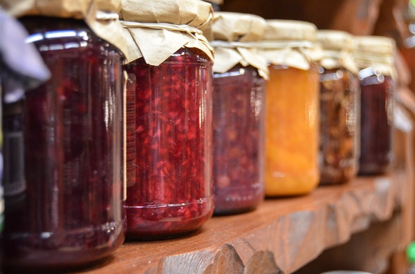 home canning jars full of preserves line a shelf