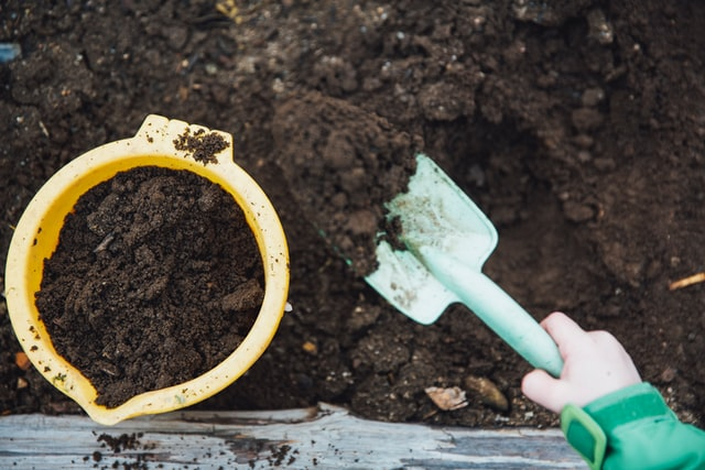 child playing with a bucket and spade and compost