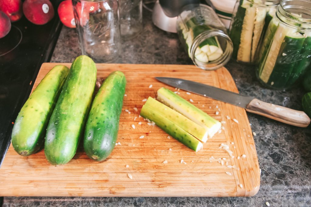 placing sliced cucumbers into mason jars for pickling